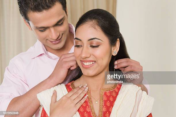 Man putting a necklace on a woman's neck