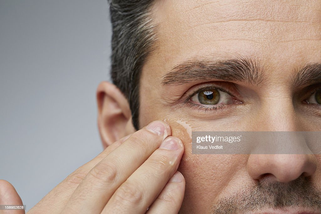 Man putting anti wrinkle gel around the eyes : Stock Photo