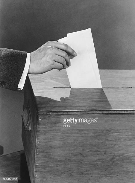 Man putting ballots into box, close up of hand