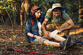 Man putting bandage on his partner knee in the jungle