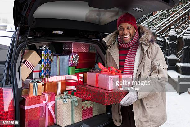 Man putting Christmas gifts in car