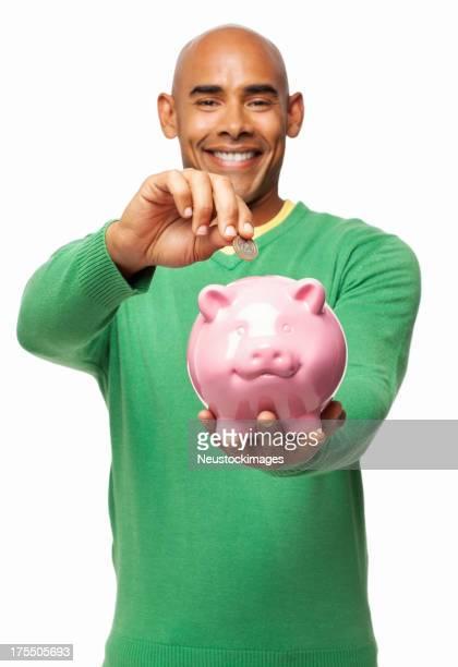 Mann setzen Münze in Sparschwein-isoliert