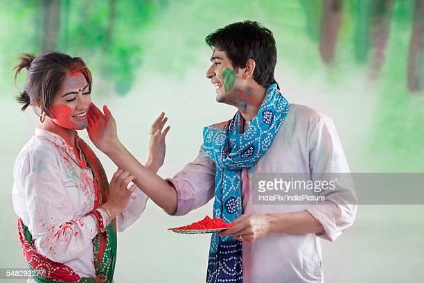 Man putting colour on a womans face