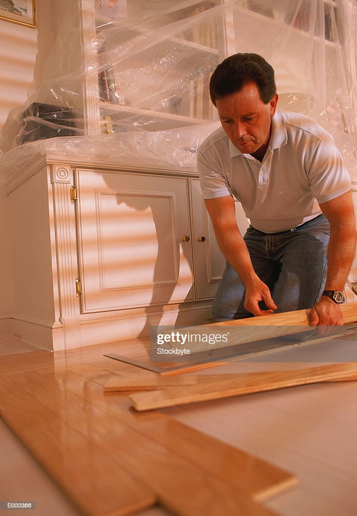 Man putting down hardwood floor : Stock Photo