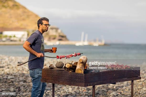 Man putting espetada skewer on grill