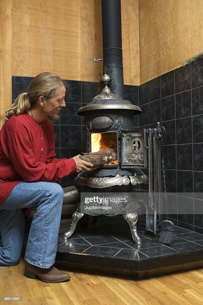 Man putting firewood into wood stove