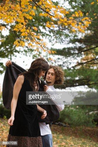Man putting jacket on woman