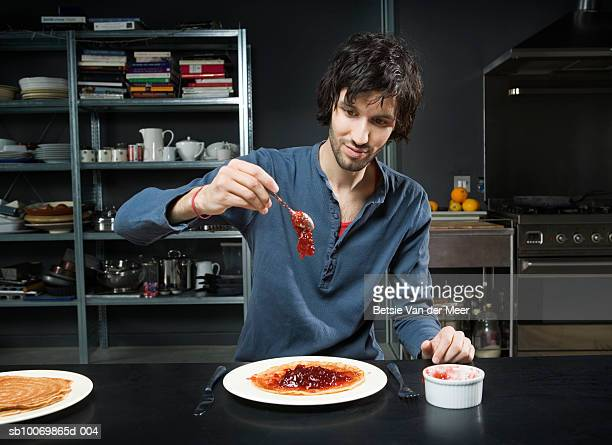 Man putting jam on pancake in kitchen