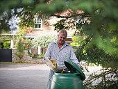 Man putting kitchen waste into compost bin