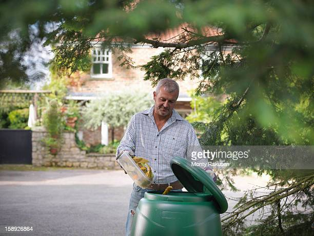 Man putting kitchen waste into compost bin