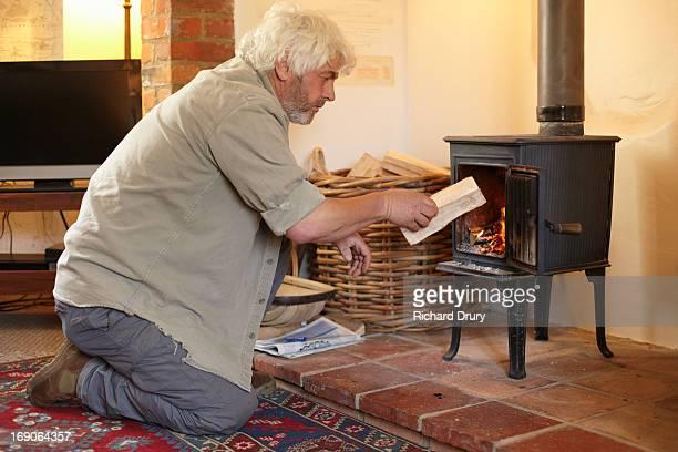 Man putting log in woodburner