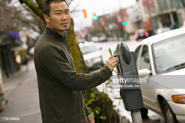 Man putting money into a parking meter