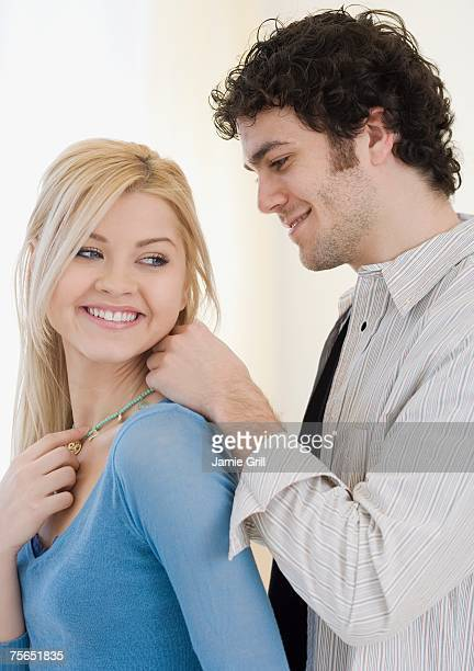 Man putting necklace on girlfriend