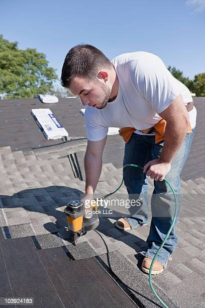 Man putting new shingles on roof