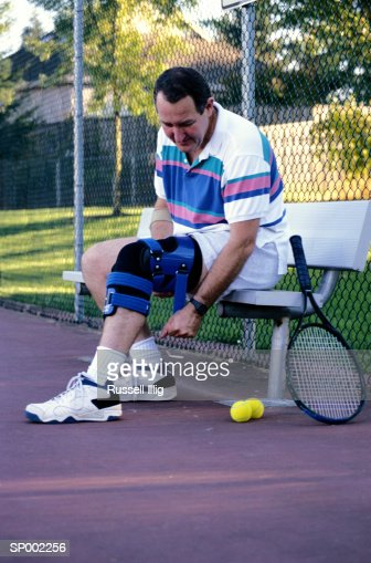 Man Putting on a Knee Brace to Play Tennis