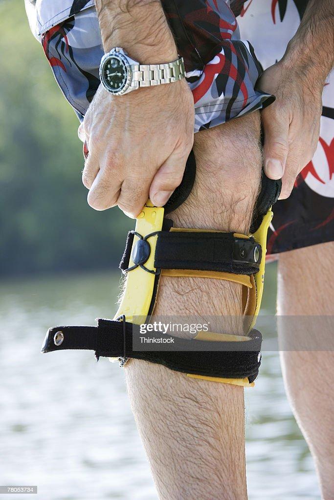 Man putting on knee brace