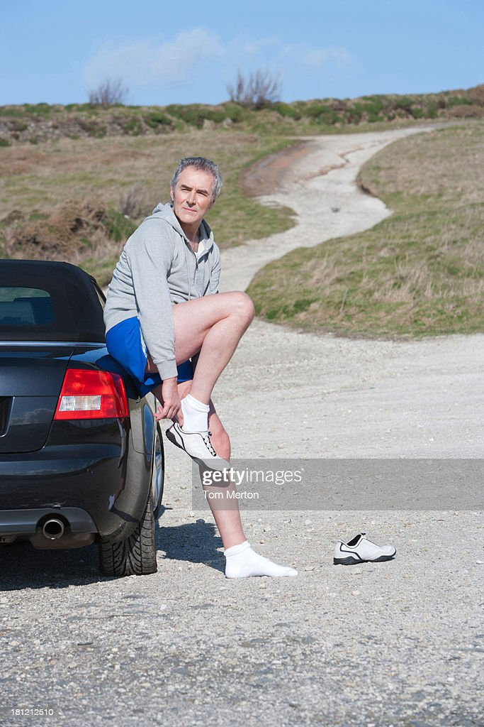Man putting on running shoes : Stock Photo