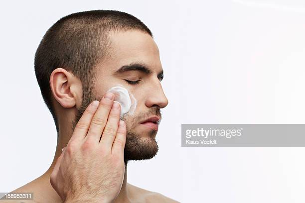 Man putting on skin cream in the face, eyes closed