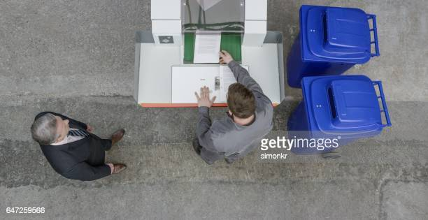 Man putting paper in shredder