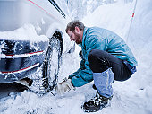 Man putting snow chains on tire.