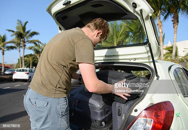 Man putting suitcases in a car
