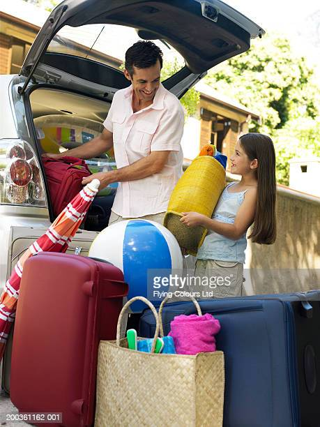 Man putting suitcases into boot of car, daughter (8-10) helping