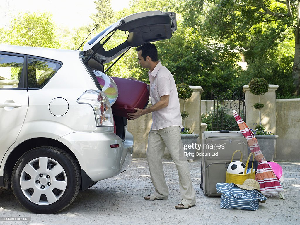 Man putting suitcases into boot of car, side view