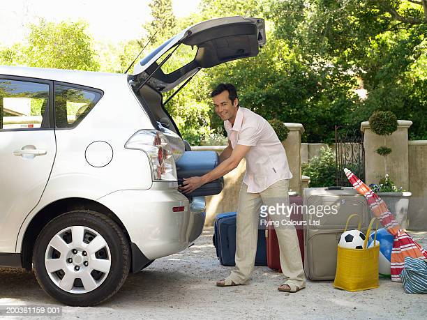 Man putting suitcases into boot of car, smiling, portrait