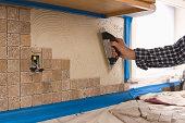 man putting tile on wall