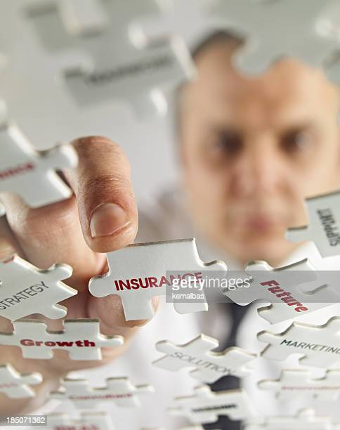 A man putting together a puzzle of insurance pieces