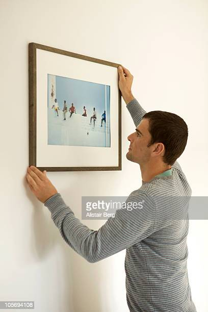 Man putting up picture