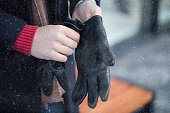 Man putting winter gloves on outside while it's snowing