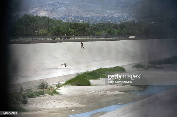 A man races back up a concrete embankment on the south side of the Rio Grande after attempting to cross the USMexico border illegally June 26 2007 in...