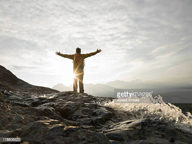 Man raises arms to sunrise over mountains, water