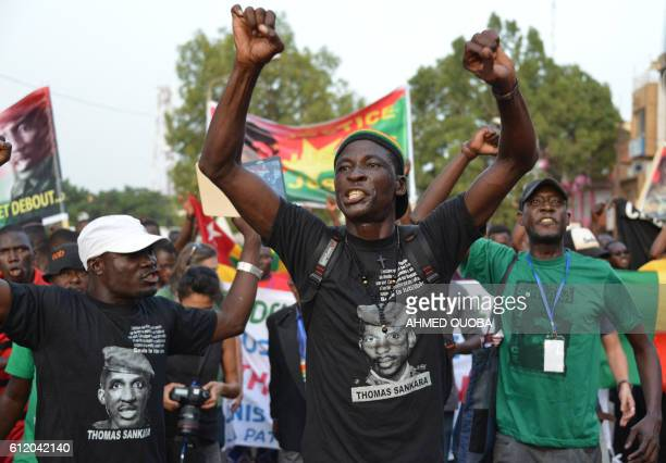 A man raises his arms as he attends a protest in tribute to Thomas Sankara in Ouagadougou on October 2 2016 Thomas Sanakara a Burkinabe military...
