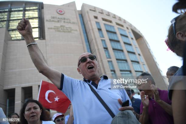 A man raises his fist as he chants slogans during a demonstration on July 24 2017 outside Istanbul's courthouse where journalists and directors of...