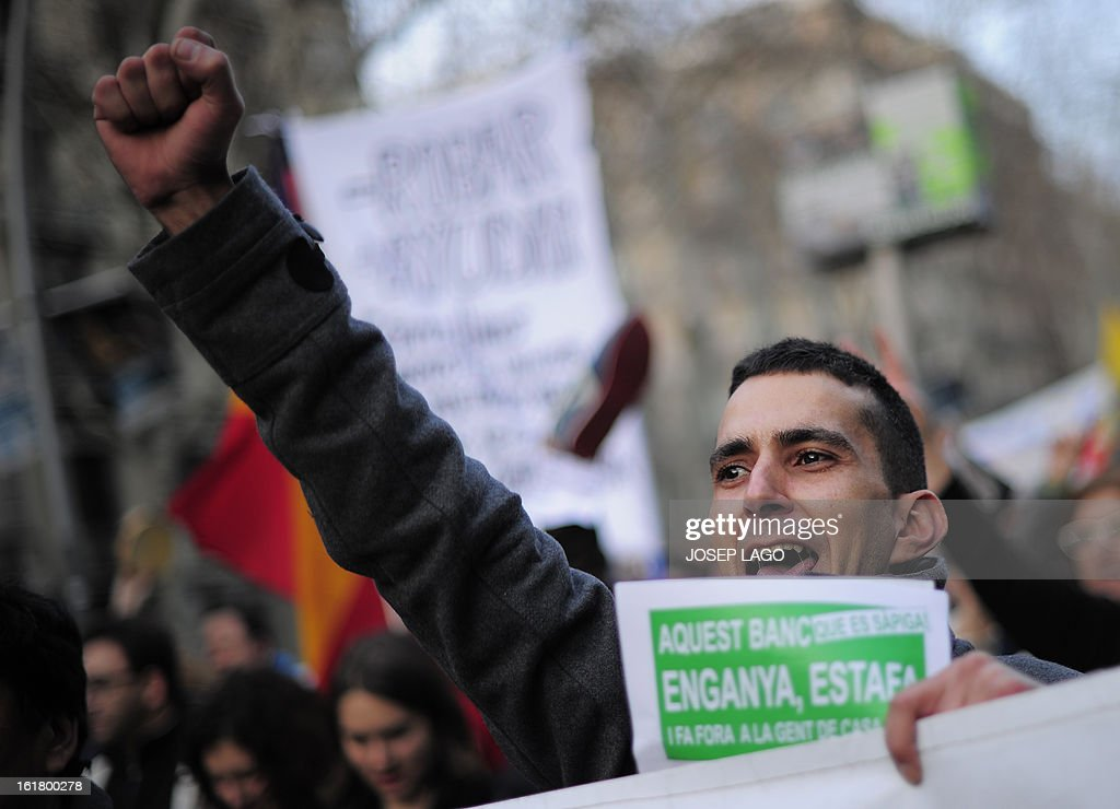 A man raises his fist during a demonstration called by the organisation Platform for Mortgage Victims (PAH) to push for a new law to end a wave of evictions of homeowners ruined by the economic crisis, on February 16, 2013 in Barcelona. Similar protests were called in 50 other Spanish cities, the latest of months of demonstrations driven by anger at Spain's recession and the conservative government, which is imposing austere economic reforms. Campaigners passed a rare milestone on February 12, 2013 when the Spanish parliament agreed to debate a popular bill of measures to protect poor homeowners, backed by a petition that received more than 1.4 million signatures. AFP PHOTO/ JOSEP LAGO