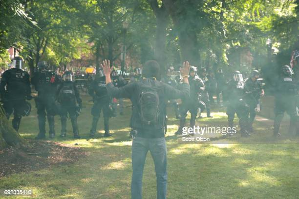 A man raises his hands as police clash with demonstrators as they try to clear 'Antifa' members and antiTrump protesters from the area during a...