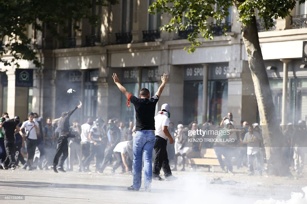 A man raises his hands as rioters clash with French riot police officers, on the Republique square in Paris, during a banned demonstration against Israel's military operation in Gaza and in support of the Palestinian people, on July 26, 2014. French authorities banned on July 26, 2014 a new pro-Palestinian demonstration over concerns it could turn violent as previous rallies have, but demonstrators may ignore the ban as they did last weekend. US Secretary of State John Kerry and other top diplomats from Europe and the Middle East began talks in Paris on July 26 to press efforts for a long-term ceasefire between Israel and Hamas.