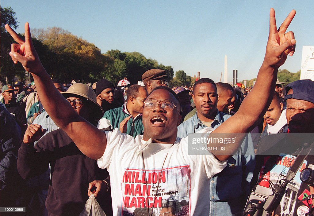 A man raises his hands in the air as he celebrates during Million Man March on the Mall, 16 October 1995, in Washington DC. The march, which was called by Nation of Islam leader Louis Farrakhan, is intended as a day for black men to unite and pledge self-reliance and commitment to their families and communities.