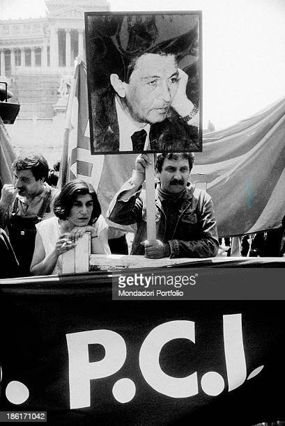 A man raising a sign with the picture of the General Secretary of the Italian Communist Party Enrico Berlinguer the day of his funeral Rome 13th June...