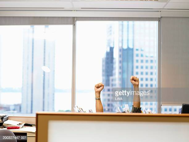 Man raising arms in cubicle, high section
