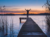 Man on a jetty raising arms during sunset as a sign of achievement