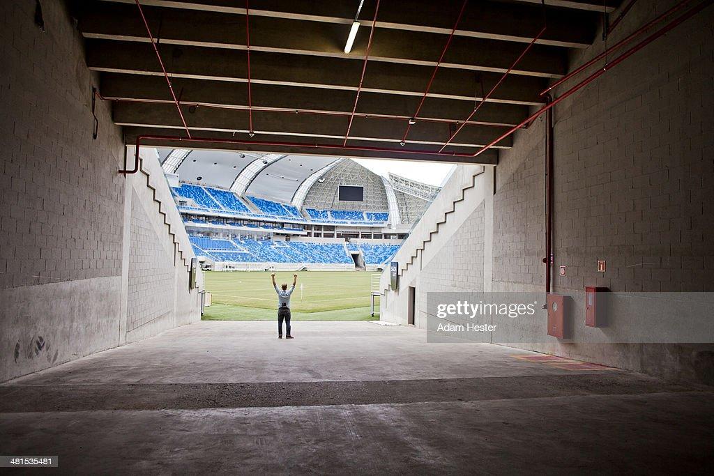 A man raising his arms inside of Arena das Dunas.
