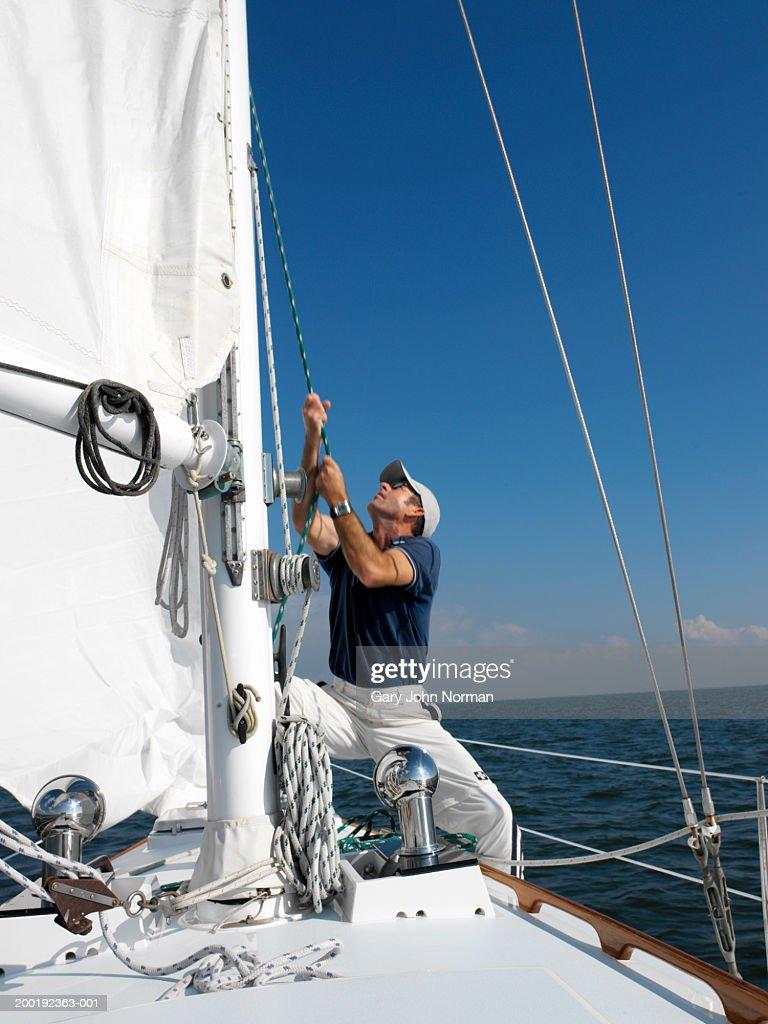 Man raising sail on boat