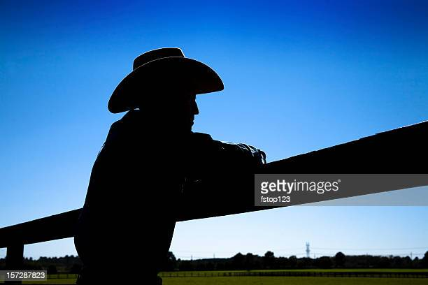 Man rancher on farm. Fence in silhouette. Cowboy hat.  Ranch.