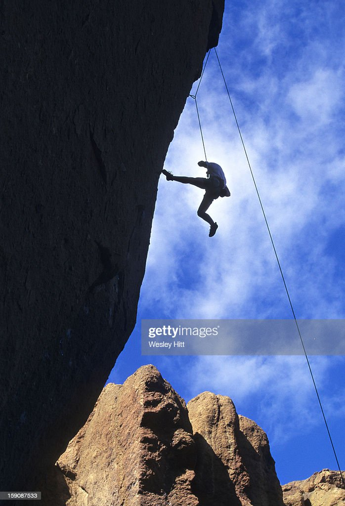A man rapelling down a cliff : Stock Photo