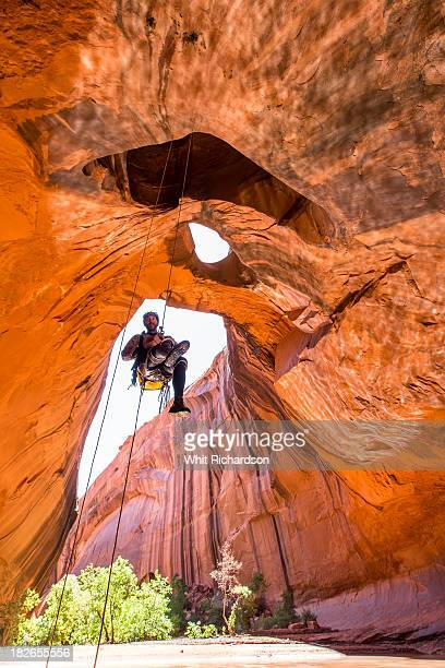 A man rapelling while canyoneering in a desert canyon.