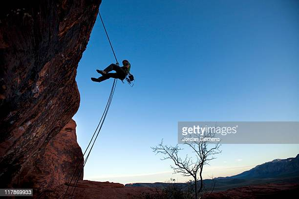 Man rappelling at sunset.