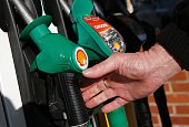 A man reaches for an unleaded petrol nosel at a fuel pump outside a Royal Dutch Shell petrol station in Hook near Basingstoke on January 20 2016...